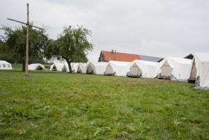 Blick vom Waldrand auf die Sclafzelte und das Lagerkreuz